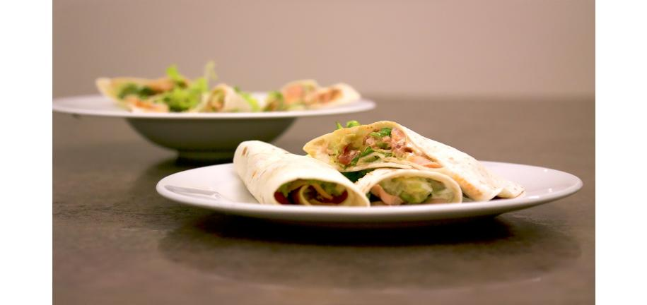 Blackend Salmon Fajitas in wraps on a plate on a table